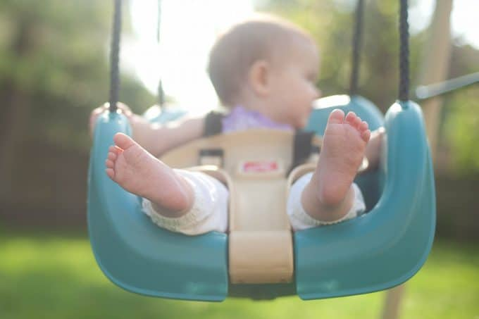 baby feet in a blue swing with the focal point on the feet and not the babies face.